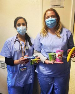 Two masked nurses with snack nags