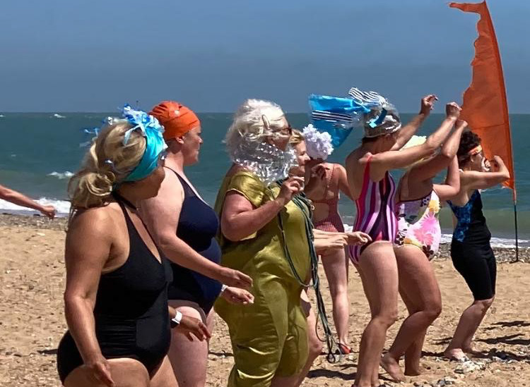 Eight women in costume dancing on the beach