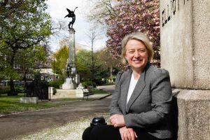 Natalie Bennett sitting near a statue in a park