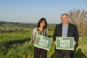 """Hawarun Hussain and Andrew Cooper holding """"Vote Green Party"""" boards in the Tong Valley"""